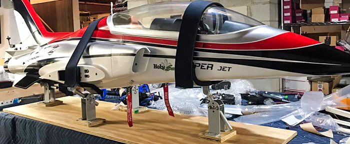 Red RC Viper jet airplane secured (tied down) in workshop (workstand)using Random Heli Gear Jacks Fuselage Support Assemblies