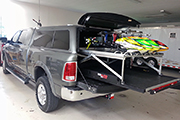 RC Helicopters on pick up truck bedslide secured for transport using Random Heli Skid Clamps
