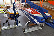 Two large RC airplanes secured for transport in trailer using Random Heli Gear Jacks
